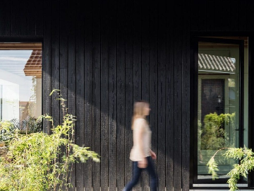 Lady walking past building with PermaChar timber cladding - charred timer cladding