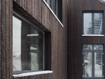 Building in the snow with charred timber cladding - PermaChar treatment - charred level: dusk